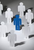 Group of similar paper men with a blue one stock photos