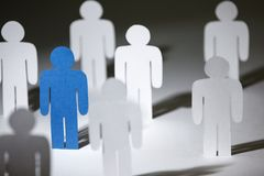 Group of similar paper people with a blue one. Close up of group of standing paper people. Lots of similar copies of a paper man, but a blue one stands out among stock photography
