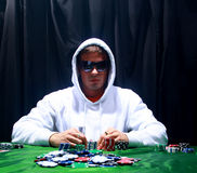 Group of sinister poker. A poker player sitting at a table trying to hide his expressions Stock Photos