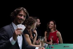 Group of sinister poker players. Poker players in casino with cards and chips on black background Royalty Free Stock Photo