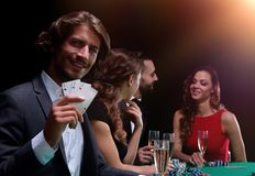 Group of sinister poker players. Poker players in casino with cards and chips on black background Royalty Free Stock Image