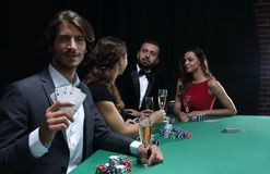 Group of sinister poker players. Poker players in casino with cards and chips on black background Stock Image
