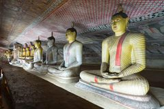 Group of sitting Buddha statues in cave buddhist temple. With bright painted murals on walls and ceiling  in Dambulla Golden temple in Sri Lanka Stock Photos