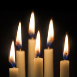 Group of six burning candles against black background, selected Royalty Free Stock Images