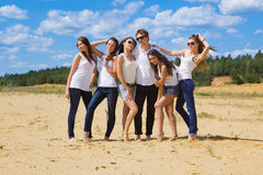 Group of six friends all in blue jeans and white. On the beach Stock Photo