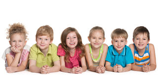 Group of six smiling children. Are lying on the floor on the white background stock photography