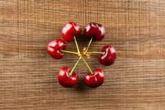 Fresh raw red sweet cherry on brown wood. Group of six whole sweet bright red cherry in a circle flatlay on brown wood stock image