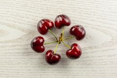 Fresh raw red sweet cherry on grey wood. Group of six whole sweet bright red cherry in a circle flatlay on grey wood stock photo