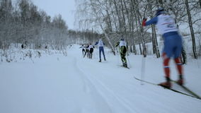 Group of skiers athletes uphill skate skiing stock video