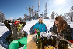 Group skiers enjoying in cafe outdoor. Group skiers enjoying together in cafe outdoor on ski terrain Stock Photo