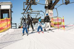 Group of skiers getting down from a ski lift on a sunny day. In Austrian Alps Royalty Free Stock Photography