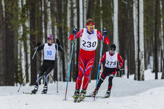 Group of skiers male athletes running through woods. Kyshtym, Russia -  March 26, 2016: group of skiers male athletes running through woods during Championship Stock Photography