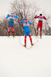 Group of skiers negotiates a hill Stock Photos
