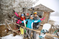 Group of skiers in winter wooden house. Group of skiers in front of winter wooden house on vacation Stock Photography