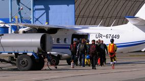 Group of skydivers goes to the plane parked near the hangar on a small airfield. Mayskoe, Dnepr, Oktober 14, 2018: Group of skydivers goes to the plane parked stock footage