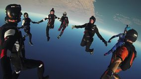 Group of skydivers jump from airplane, make formation in blue sky. Sun. Extreme