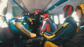 Group of skydivers sits inside a small plane awaiting a jump. Slow Motion. Mayskoe, Dnepr, Oktober 14, 2018: Group of skydivers sits inside a small plane stock video footage