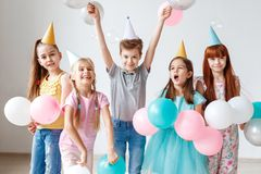 Group of small children have birthday party, wear festive hats, hold balloons, have joy together, enjoy playing games. Small adorable girl celebrates her Royalty Free Stock Image