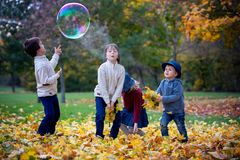 Group of small children in the park, having fun throwing leaves Stock Photography