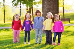 A group of small children smiling holding hands on a background of grass, a tree and a park. stock photos