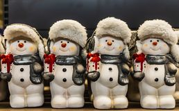 A group of small fun snowmen toys with hats and smile. Are on the dack background royalty free stock images