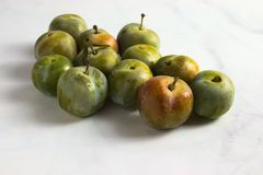 Group of small greengage plums on white marble stock images
