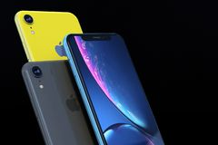 Product shot of iPhone XR blue and yellow on black background. Group of 3 smartphones - iPhone XR Blue, Yellow and Space gray, arranged in a formation of three royalty free stock photography