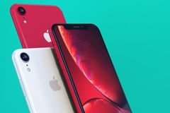 Product shot of iPhone XR Red on green background close-up royalty free stock photo