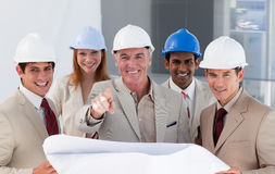 A group of smiling architects studying blueprints. In a building Royalty Free Stock Images