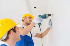 Group of smiling builders with drill indoors Stock Photo