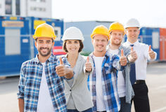 Group of smiling builders in hardhats outdoors Stock Image