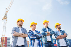 Group of smiling builders in hardhats outdoors Stock Images
