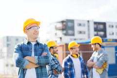 Group of smiling builders in hardhats outdoors Royalty Free Stock Images