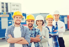 Group of smiling builders in hardhats outdoors. Business, building, teamwork and people concept - group of smiling builders in hardhats outdoors Stock Photo