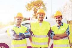 Group of smiling builders in hardhats outdoors. Business, building, teamwork and people concept - group of smiling builders in hardhats on car background Stock Image