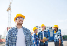 Group of smiling builders in hardhats outdoors Stock Photos