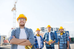 Group of smiling builders in hardhats outdoors Stock Photography