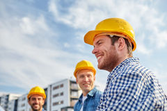Group of smiling builders in hardhats outdoors. Business, building, teamwork and people concept - group of smiling builders in hardhats at construction site Royalty Free Stock Photography