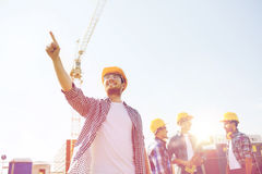 Group of smiling builders in hardhats outdoors. Business, building, teamwork and people concept - group of smiling builders in hardhats pointing finger outdoors Royalty Free Stock Photos