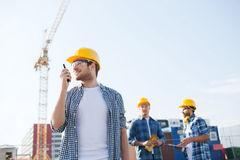 Group of smiling builders in hardhats with radio Royalty Free Stock Photo