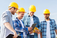 Group of smiling builders with tablet pc outdoors Royalty Free Stock Photos