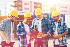 Group of smiling builders with tablet pc outdoors. Business, building, teamwork, technology and people concept - group of smiling builders in hardhats with Stock Photography