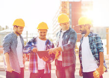 Group of smiling builders with tablet pc outdoors. Business, building, teamwork, technology and people concept - group of smiling builders in hardhats with stock photo