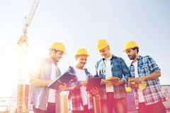 Group of smiling builders with tablet pc outdoors royalty free stock images