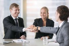 A group of smiling business leaders giving high five. Group of business people, giving high five, forming new relationship with business partner, successful stock images