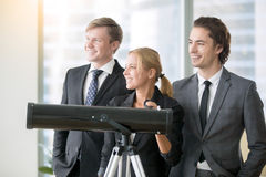 Group of smiling business people with optic telescope royalty free stock photo