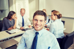 Group of smiling businesspeople meeting in office. Business, people and teamwork concept - smiling businessman with group of businesspeople meeting in office stock photography