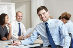Group of smiling businesspeople meeting in office. Business, people and teamwork concept - smiling businessman with group of businesspeople meeting in office Royalty Free Stock Image