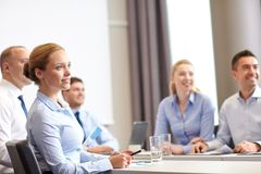Group of smiling businesspeople meeting in office. Business, people and teamwork concept - group of smiling businesspeople meeting on presentation in office stock image