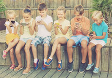 Group of smiling children playing with mobile phones outdoors Stock Photography